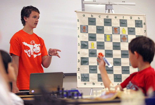 Lennie Mahler  |  The Salt Lake Tribune Kayden Troff, 14, instructs young chess players on how to keep pieces coordinated to block opponents' moves during a lesson at the McGillis School on Monday, June 25, 2012. Troff was selected for the