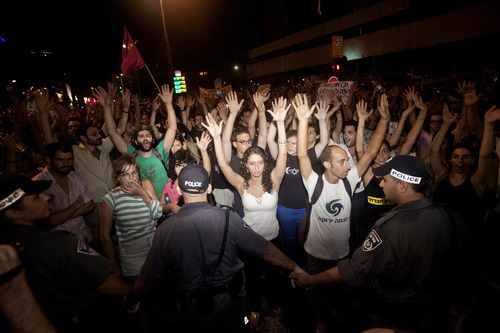 Israeli activists raise their hands during a social protest in Tel Aviv, Israel early Sunday, June 24, 2012. Israeli police say 85 protesters were arrested on Saturday after clashing with officers and vandalizing banks in Tel Aviv. (AP Photo/Dan Balilty)