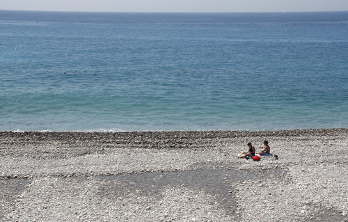 People sunbathe on the beach in Nice, southern France, Tuesday, June 26, 2012. Temperatures are close to 30 degrees Celsius (86 Fahrenheit). (AP Photo/Lionel Cironneau)