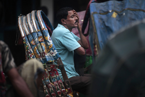 A man reacts as he is stuck on a rickshaw in a huge traffic jam in Dhaka, Bangladesh, Sunday, June 24, 2012. (AP Photo/Saurabh Das)