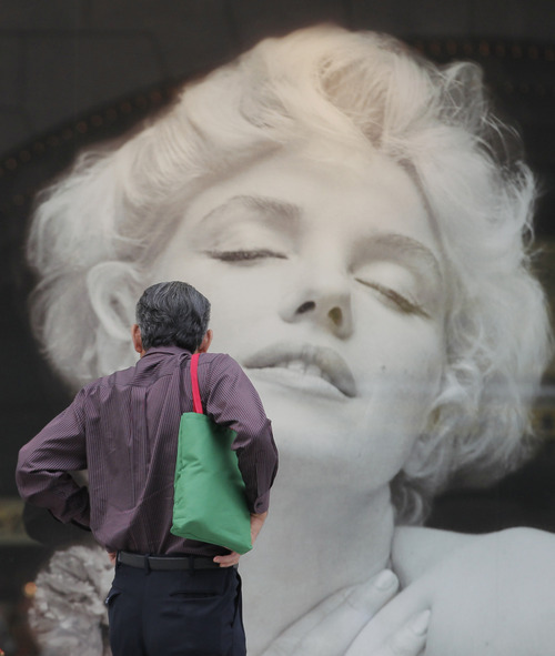 A man looks at a display of Marilyn Monroe picture outside a boutique at Ginza shopping district in Tokyo, Sunday, June 24, 2012. (AP Photo/Shizuo Kambayashi)