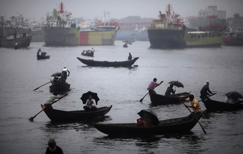 People take out their umbrellas as it starts raining while crossing Buriganga river in Dhaka, Bangladesh, Sunday, June 24, 2012. Hundreds of thousands of people use boats to commute from one part of the country to another as well as inside cities in Bangladesh, a largely riverine country. (AP Photo/ Saurabh Das)