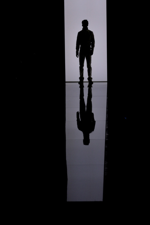 A model is silhouetted on the runway as he wears a creation of Bottega Veneta from the men's Spring-Summer 2013 collection as part of the Milan Fashion Week, unveiled in Milan, Italy, Sunday, June 24, 2012. (AP Photo/Luca Bruno)