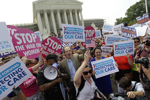 Supporters of President Barack Obama's health care law celebrate outside the Supreme Court in Washington, Thursday, June 28, 2012, after the court's ruling. AP Photo/David Goldman)