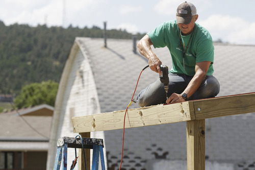 In this Tuesday, June 26, 2012, photo, Greg Boothe, a contractor from Dallas, works on building a stage at the Dakota Transitional Head Start in north Rapid City, S.D. Boothe, who was volunteering with a Christian group called Mission Discovery, said of Tuesday's heat,