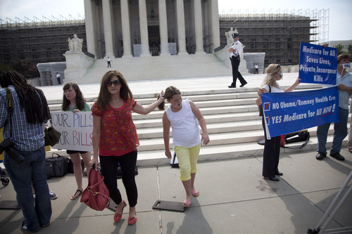 People wait outside the Supreme Court in Washington, Monday, June 25, 2012. The Supreme Court is meeting Monday to issue opinions in some of the handful of cases that remain unresolved.  (AP Photo/Evan Vucci)