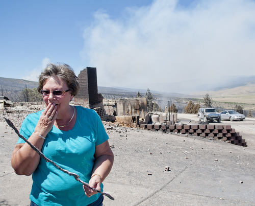 Michael Mangum     Special to the Tribune  With smoke from the Wood Hollow wildfire still billowing in the background, Indianola resident Janice Taylor reacts as she walks through her property after flames completely engulfed and destroyed her home and everything on the property on Wednesday, June 27, 2012.