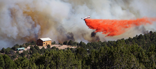 Kyle Kester  |  Special to The Salt Lake Tribune  A plane drops fire retardant near a home in New Harmony on Wednesday, June 27, 2012.