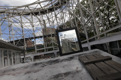 In a Tuesday, June 26, 2012 photo taken on Coney Island in New York, a reflection of the first and steepest climb is seen in a mirror placed near the tracks of the Cyclone roller coaster.  (AP Photo/Mary Altaffer)