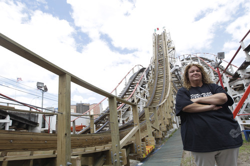 In a Tuesday, June 26, 2012 photo taken on Coney Island in New York, Jennifer Tortorici the operations manager of the Cyclone roller coaster poses for a photo.  The New York City landmark and international amusement icon will be feted Saturday, June 30 with a birthday party in its honor.    (AP Photo/Mary Altaffer)