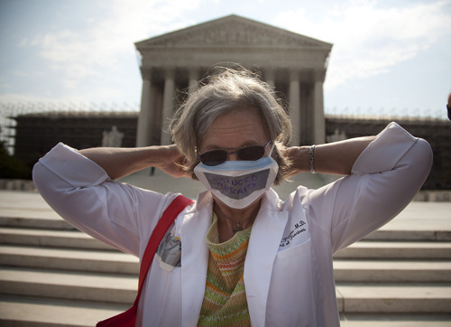 In this photo taken, Monday, June 25, 2012, Carol Paris of Leonardtown, Md. demonstrates outside the Supreme Court in Washington. On Thursday the Supreme Court will deliver their ruling on President Barack Obama's health care package. (AP Photo/Evan Vucci)