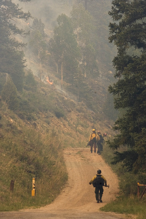 Paul Fraughton  |  The Salt Lake Tribune Firefighters work near the historic Stuart Guard Station in Huntington Canyon on Wednesday, June 27, 2012, as the Seeley fire continues to burn in the Manti-La Sal National Forest.