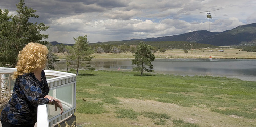 Paul Fraughton   Salt Lake Tribune Darlene Mortensen who lives on Day Road, north of Fairview watches from her deck as helicopters dip their buckets into her pond.  Bennett was evacuated  earlier along with residents of Fairview. She returned to the house and was allowed to stay because firefighters felt she was in  a safe location due to the fact that the helicopters could douse her house if flames got to close.   Thursday, June 28, 2012