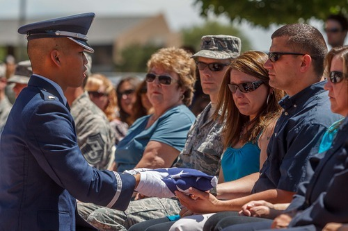 Trent Nelson  |  The Salt Lake Tribune Lt. Danny Chung of the Hill Air Force Base Honor Guard presents a flag to Christa and Nathan Stull in memory of Marco, a military working dog, during a retirement ceremony for four military working dogs held by the 75th Air Base Wing Security Forces at Hill Air Force Base on Friday, June 29, 2012.