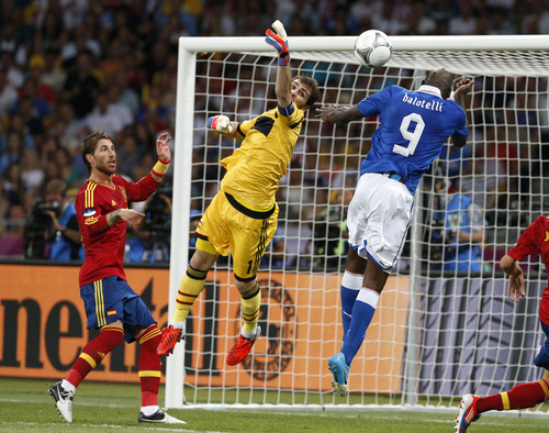 Spain goalkeeper Iker Casillas, center, clears the ball from Italy's Mario Balotelli, right, during the Euro 2012 soccer championship final  between Spain and Italy in Kiev, Ukraine, Sunday, July 1, 2012. (AP Photo/Michael Sohn)