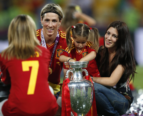 Spain's Fernando Torres, his wife Olalla, right, pose with the trophy for a photograph after Spain won the Euro 2012 soccer championship final  between Spain and Italy in Kiev, Ukraine, Monday, July 2, 2012. (AP Photo/Jon Super)