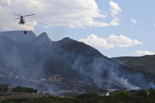 Chris Detrick  |  The Salt Lake Tribune Helicopters work to help put out the Rose Crest Fire around Herriman Friday June 29, 2012. As of about 7 p.m. the fire was estimated at 200 acres in size and at zero containment.