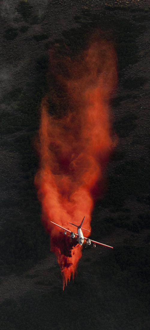Jeremy Harmon  |  The Salt Lake Tribune  A plane dumps retardant on the fire in the foothills above Herriman on Friday, June 29, 2012.