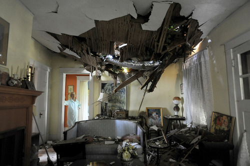 Frances Lukens looks at the tangle of boards and tree limbs piercing her living room ceiling in Lynchburg, Va. on Saturday, June 30, 2012 after a huge oak tree fell directly on the house during a storm the previous night. (AP Photo/The News & Advance, Parker Michels-Boyce)