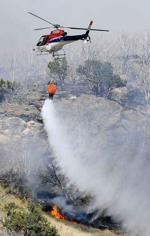 A helicopter drops water on a fire near the mouth of Millville Canyon on Sunday. (Eli Lucero/Herald Journal)