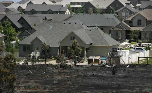 Scott Sommerdorf  |  The Salt Lake Tribune              Firefighters stopped the advance of the fire just yards from some homes on the west edge of Herriman Sunday, July 1, 2012.