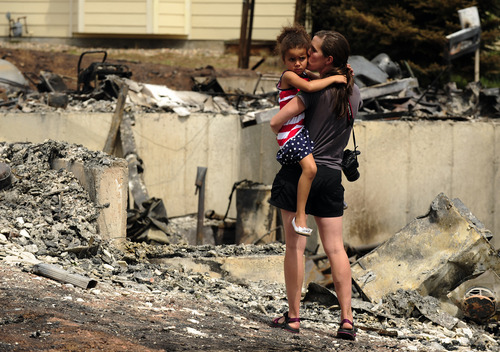 Melissa Mgana kisses her young daughter Sofia, 5, as she surveys what is left of their home Sunday, July 1, 2012, into the Mountain Shadows subdivision of Colorado Springs, Colo., after the Waldo Canyon fire ravaged the neighborhood. Her husband Immanuel had been deployed in the army in East Africa but was allowed to return home when he got word of the damage. So far, the blaze, now 45 percent contained, has damaged or destroyed nearly 350 homes. (AP Photo/The Denver Post, Helen H. Richardson)  MAGS OUT; TV OUT; INTERNET OUT