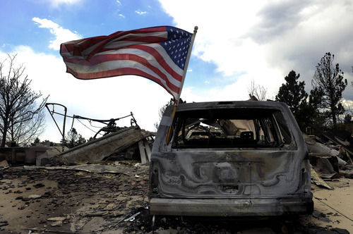 A United States flag flies on a burnt car as residents were allowed back on Sunday, July 1, 2012, into the Mountain Shadows subdivision of Colorado Springs, Colo., to visit their homes after the Waldo Canyon fire ravaged the neighborhood. So far, the blaze, now 45 percent contained, has damaged or destroyed nearly 350 homes. (AP Photo/The Denver Post, Helen H. Richardson)  MAGS OUT; TV OUT; INTERNET OUT
