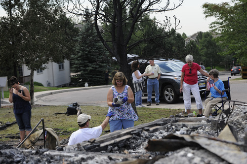 Cortney Lee, left, looks over what is left of her great aunt's home Sunday, July 1, 2012, in the Mountain Shadows subdivision of Colorado Springs, Colo., after the Waldo Canyon fire ravaged the neighborhood. So far, the blaze, now 45 percent contained, has damaged or destroyed nearly 350 homes.  (AP Photo/The Denver Post, Heather Rousseau)  MAGS OUT; TV OUT; INTERNET OUT