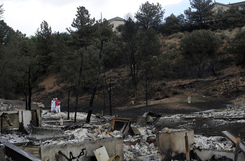Jerry Lidenberg, 75, and his wife Beth , 71, look over the ashes of the home they lived in for 19 years on Sunday, July 1, 2012, in the Mountain Shadows subdivision of Colorado Springs, Colo., after the Waldo Canyon fire ravaged the neighborhood. So far, the blaze, now 45 percent contained, has damaged or destroyed nearly 350 homes.  (AP Photo/The Denver Post, Heather Rousseau)  MAGS OUT; TV OUT; INTERNET OUT