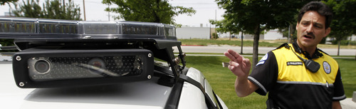Al Hartmann  |  The Salt Lake Tribune  Ogden Police Officer Tim Shelstead points to one of the four rooftop cameras that are placed beneath the light bar on a specially equipped Ogden police car that can read license plates in real time. Agencies around the state are using license plate scanners to aid highway and street patrol cars in apprehending criminals.