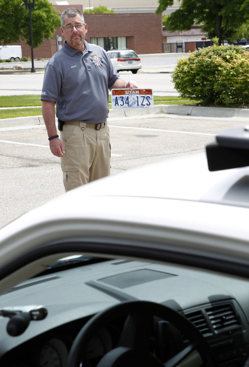 Al Hartmann  |  The Salt Lake Tribune  Ogden Police crime analyst Dave Weloth holds a license plate to be read by a specially equipped Ogden police car that can read license plates in real time. Agencies around the state are using license plate scanners to aid highway and street patrol cars in apprehending criminals.