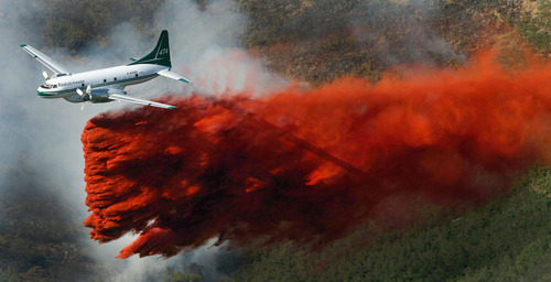 Steve Griffin | The Salt Lake Tribune A plane drops its payload of fire retardant on a fire that burns just above homes in the mountains near Alpine on Tuesday July 3, 2012.
