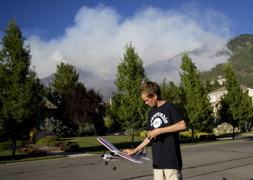 Kim Raff | The Salt Lake Tribune Brendon Boyd plays with a model plane similar to the ones used to battle the Quail Wildfire that burns in the background in Alpine on Tuesday July 3, 2012.
