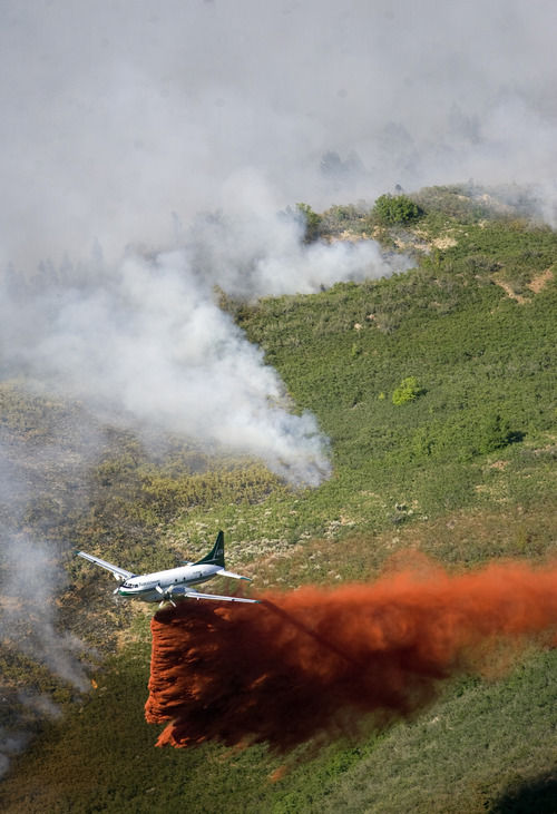 Kim Raff | The Salt Lake Tribune An airplane drops flame retardant on the Quail Wildfire in Alpine on Tuesday July 3, 2012.
