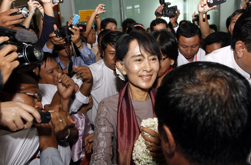 CORRECTS YEAR OF THE DATE - Myanmar opposition leader Aung San Suu Kyi, center, is welcomed by supporters upon her arrival at Yangon International Airport in Yangon, Myanmar Saturday, June 30, 2012. Cheering crowds welcomed Suu Kyi home Saturday from her triumphant tour of Europe, where she won enthusiastic support for her role in Myanmar's democratic transition and was celebrated like a head of state. (AP Photo/Khin Maung Win)