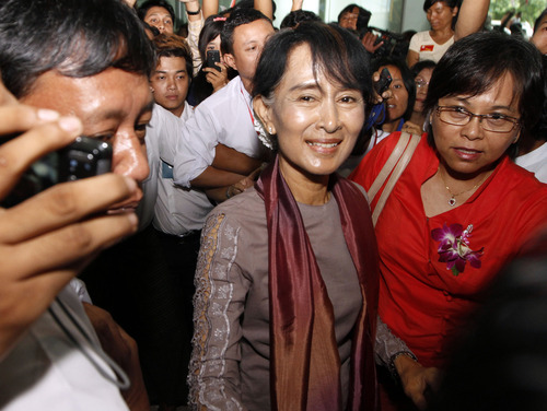Myanmar opposition leader Aung San Suu Kyi, center, arrives at Yangon International Airport in Yangon, Myanmar Saturday, June 30, 201. Cheering crowds welcomed Suu Kyi home Saturday from her triumphant tour of Europe, where she won enthusiastic support for her role in Myanmar's democratic transition and was celebrated like a head of state. (AP Photo/Khin Maung Win)
