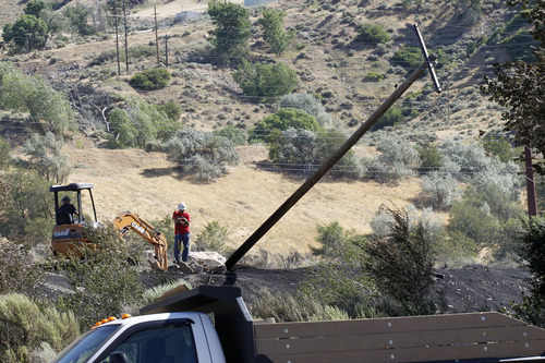 Al Hartmann     The Salt Lake Tribune Personnel work to right a leaning utility pole in the burned area next to a Rocky Mountain Power substation at the mouth of Ogden Canyon Tuesday morning July 3.