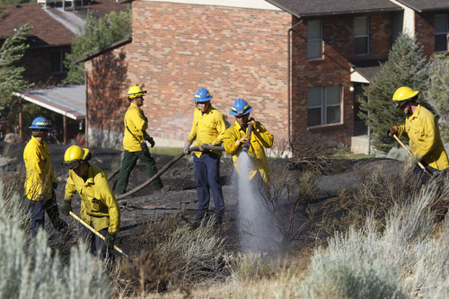 Al Hartmann     The Salt Lake Tribune Ogden firefighters put out hot spots in a field at the mouth of Ogden Canyon on Tuesday, July 3.  The fire came within a few feet of a condominium complex behind them to the east.