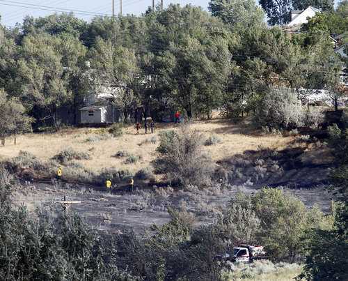 Al Hartmann     The Salt Lake Tribune Ogden City fire fighters mop up and put out hot spots in field at the mouth of Ogden Canyon Tuesday morning July 3.  The fire came within a few feet of a condominium complex behind them to the east.