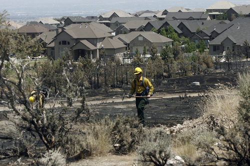 Scott Sommerdorf  |  The Salt Lake Tribune              Fire crews searched for hot spots along the north edge of Chris Mitchell's parent's home on Majestic Oaks Lane in Herriman, Sunday, July 1, 2012.
