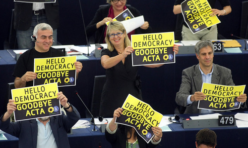 Green Party members of the European parliament demonstrate against the ACTA project (Anti-Counterfeiting Trade Agreement) during the vote Wednesday, July 4, 2012 at the European Parliament in Strasbourg, eastern France. The European Parliament has overwhelmingly defeated the international ACTA anti-piracy agreement, after fears that it would limit Internet freedom. A