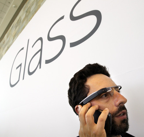 Google co-founder Sergey Brin talks on the phone as he wears Google's new Internet-connected glasses at the Google I/O conference in San Francisco, Wednesday, June 27, 2012. Google is making prototypes of the device, known as Project Glass, available to test. They can only be purchased - for $1,500 - at the conference this week, for delivery early next year. (AP Photo/Paul Sakuma)