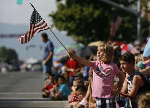 Francisco Kjolseth  |  The Salt Lake Tribune Waving her flag, 7-year-old America Johnson of Lehi joins the thousands lining the streets of downtown Provo to watch the Freedom Festival Parade on Wednesday, July 4, 2012.