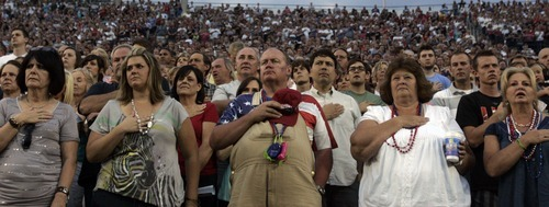 Kim Raff | The Salt Lake Tribune People stand during the National Anthem during the Stadium of Fire at the LaVell Edwards Stadium in Provo, Utah on July 4, 2012.