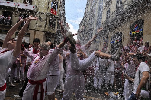 Revelers enjoy water throwing from a balcony during the 'Chupinazo', the official opening of the San Fermin fiestas in Pamplona, northern Spain, Friday, July 6, 2012 to celebrate the start of Spain's most famous bull-running festival. Perhaps best glorified by Ernest Hemingway's 1926 novel