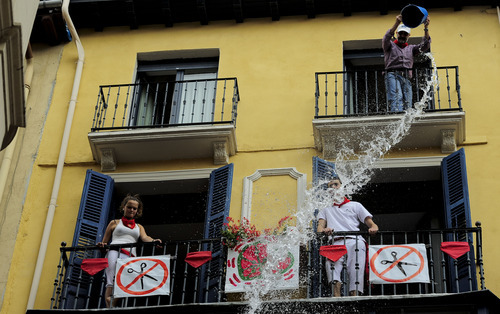 Reveler enjoys pouring water down from a balcony during the 'Chupinazo', the official opening of the San Fermin fiestas in Pamplona, northern Spain, Friday, July 6, 2012 to celebrate the start of Spain's most famous bull-running festival. Perhaps best glorified by Ernest Hemingway's 1926 novel