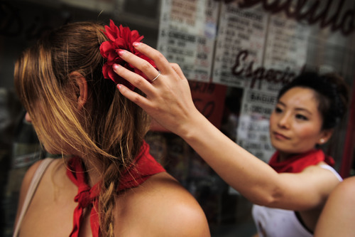 Reveler decorates a head of a woman with one carnation during the opening San Fermin fiestas, in Pamplona, northern Spain, Friday, July 6, 2012 to celebrate the start of Spain's most famous bull-running festival with the annual launch of the