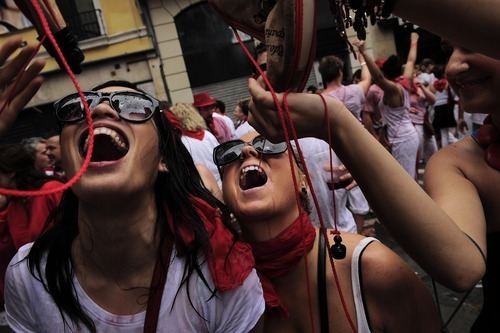 Australian revelers enjoy as they drink from a small wineskin, in Pamplona, northern Spain, Friday, July 6, 2012 to celebrate the start of Spain's most famous bull-running festival with the annual launch of the