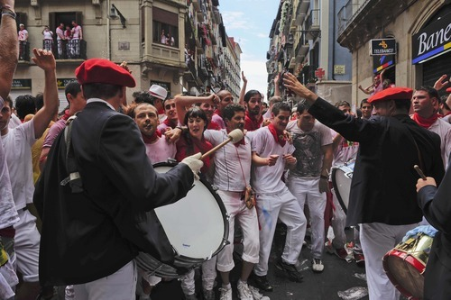 Musicians try to walk pass alongside revelers, in Pamplona, northern Spain, Friday, July 6, 2012 as they celebrate the start of Spain's most famous bull-running festival with the annual launch of the
