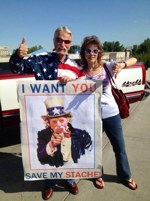 Mayor Dan Snarr and his wife April waged competing campaigns during Murray's July Fourth parade -- his to save his 18-inch handlebar mustache, hers to shave it. Judging by thumbs up, about 2/3 of the crowd sided with the mayor. Courtesy Trevor Snarr